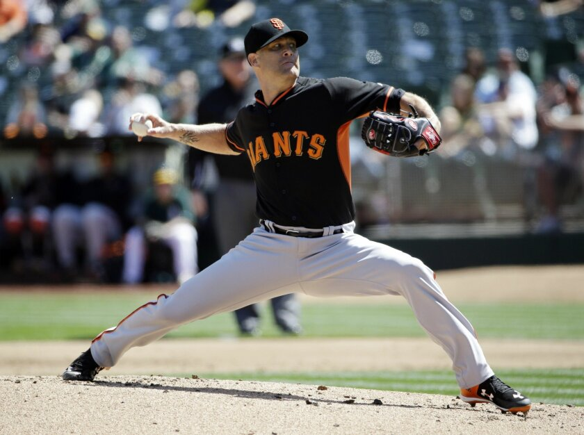 San Francisco Giants starting pitcher Tim Hudson throws to the Oakland Athletics during the first inning of an exhibition baseball game, Saturday, April 4, 2015, in Oakland, Calif. (AP Photo/Marcio Jose Sanchez)