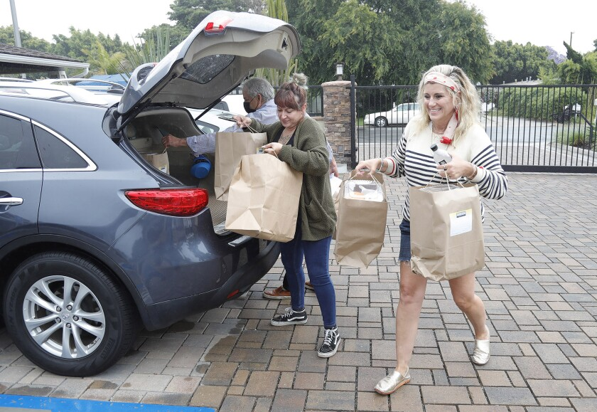 Organizer Grace Rogers, right, house chef Fatima Abuzaineh, center, and Tavern House Kitchen + Bar co-owner Gregg Solomon unload lunches donated to the New Directions for Women facility in Costa Mesa on Monday.