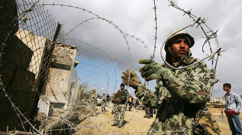 Egyptian soldiers use barbed wire to close a section of the border between the southern Gaza Strip town of Rafah and Egypt.