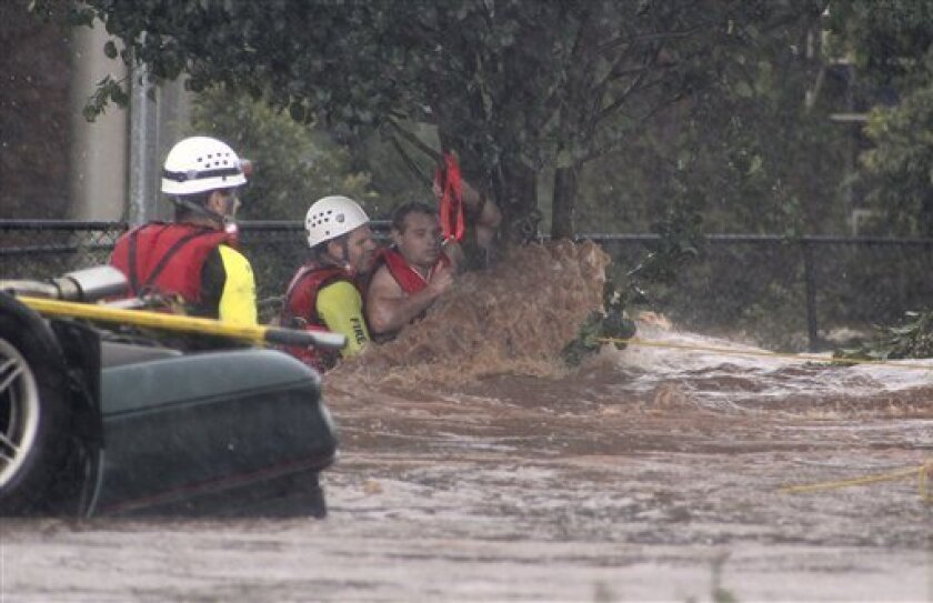 A man is rescued by emergency workers after he was stranded clinging to a tree on a flooded street in Toowoomba, Australia, during a flash flood Monday, Jan. 10, 2011. Flash floods swept through the northeastern Australian community killing one woman, trapping others in cars and leaving some clinging to trees as relentless rains brought more misery to a region battling its worst flooding in decades. (AP Photo/ABC) AUSTRALIA OUT