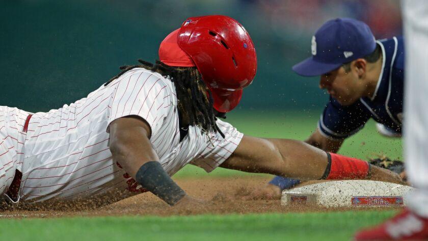 The Phillies' Maikel Franco slides safely into third base Friday night as Padres third baseman Christian Villanueva scrambles to make a tag.