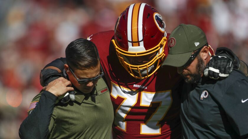 Redskins guard Shawn Lauvao is helped off the field after suffering a knee injury against the Falcons.
