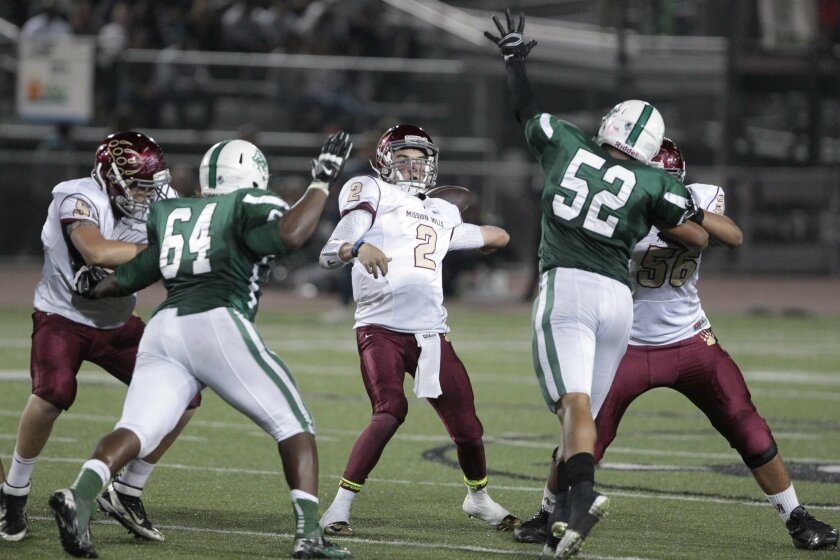 Mission Hills' quarterback Dakota Miller throws a pass while under pressure by Oceanside's Amadeo West, right, and Jamie Harris in the second quarter at Oceanside High School on Friday.