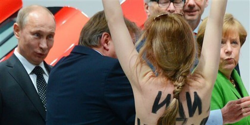 A topless demonstrator with written messages on her back walks towards Russian President Vladimir Putin , left and German Chancellor Angela Merkel, right,  during the opening tour at  the Hannover Fair in Hannover, Germany, Monday April 8, 2013. Several activists stormed the booth of Volkswagen to