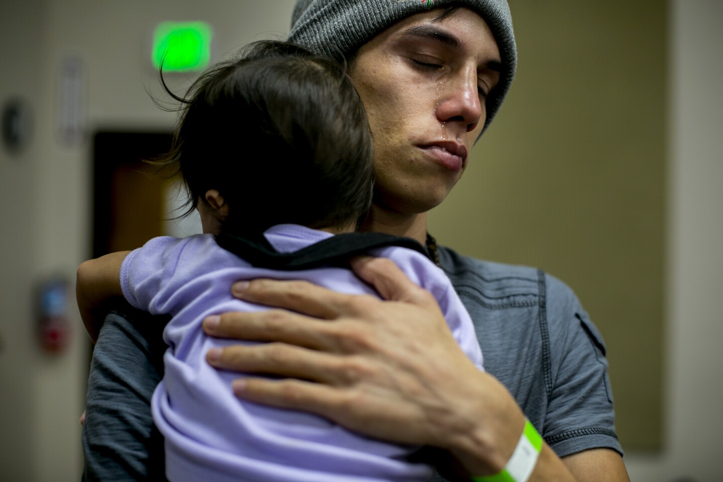 In January, Luis, 21, clutches his one-year-old daughter Grethel as he discusses his trek from Honduras and his escape from violent gangs in his home country while staying at the Rapid Response Network's shelter in San Diego for migrants who were awaiting hearings in the United States.