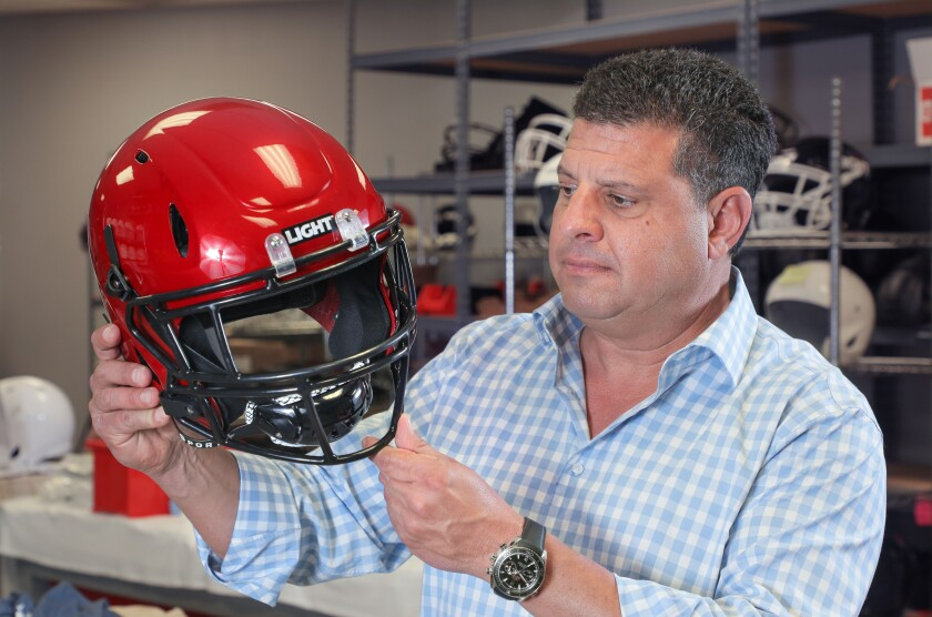 Light Helmets CEO Nick Esayian holds a copy of one of the helmets that will be tried out by the San Diego State Aztecs football team this season.