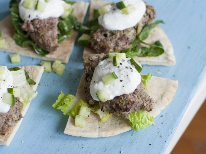 This April 28, 2014 photo shows grilled Middle Eastern lamb burgers with garlic sauce in Concord, N.H. Beef may claim to be what's for dinner in America, but in the Middle East that honor often goes to lamb. (AP Photo/Matthew Mead)