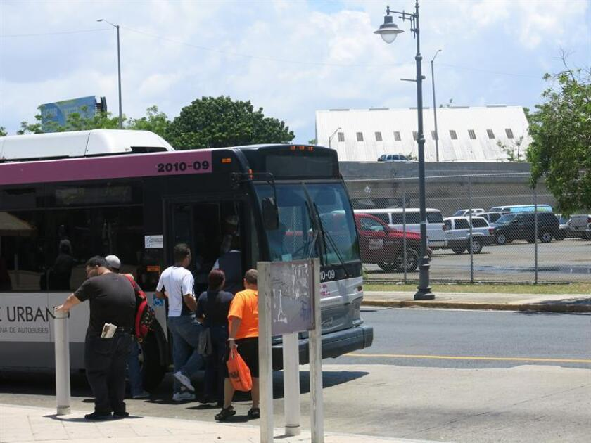 Unas personas esperan subir al autobús en San Juan, Puerto Rico. EFE/Archivo
