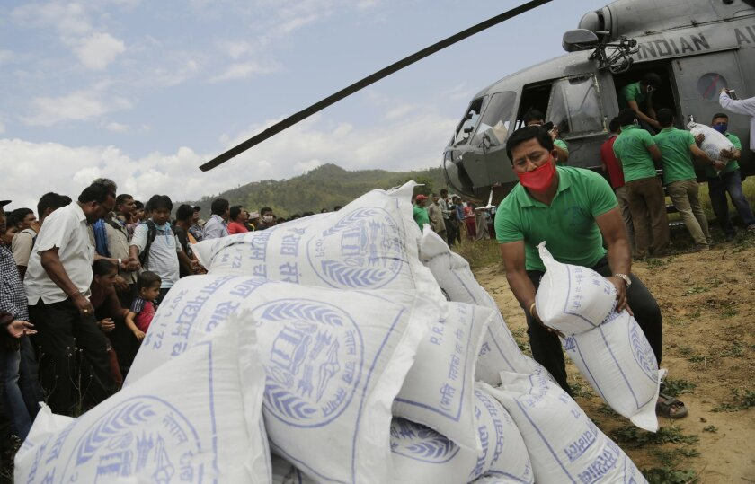 Nepalese volunteers unload relief material brought in an Indian air force helicopter for victims of Saturday's earthquake at Trishuli Bazar in Nepal, Monday, April 27, 2015. Wedged between the two rising Asian powers of China and India, landlocked Nepal saw rescuers and offers of help pour from bot