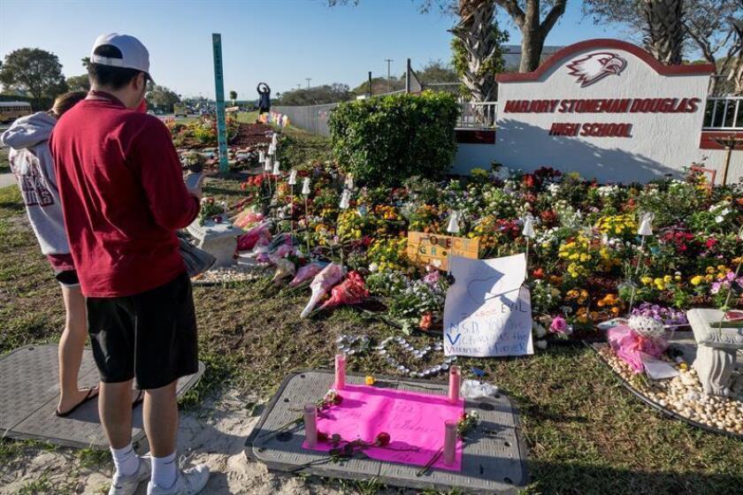 Dos personas observan el monumento improvisado en conmemoración del tiroteo de hace un año en el instituto Marjory Stoneman Douglas, el jueves 14 de febrero de 2019 en Parkland, Florida (Estados Unidos). EFE/Archivo