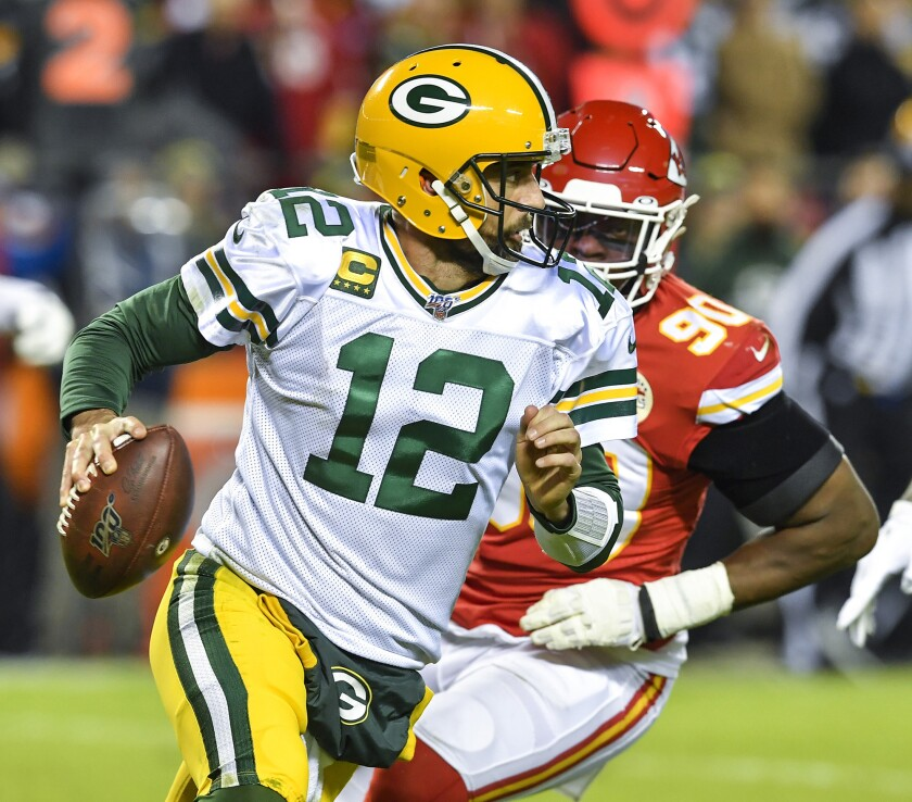 Green Bay Packers quarterback Aaron Rodgers (12) is chased out of the pocket in the second quarter by Kansas City Chiefs defensive end Emmanuel Ogbah in Kansas City, Mo., on Oct. 27, 2019.