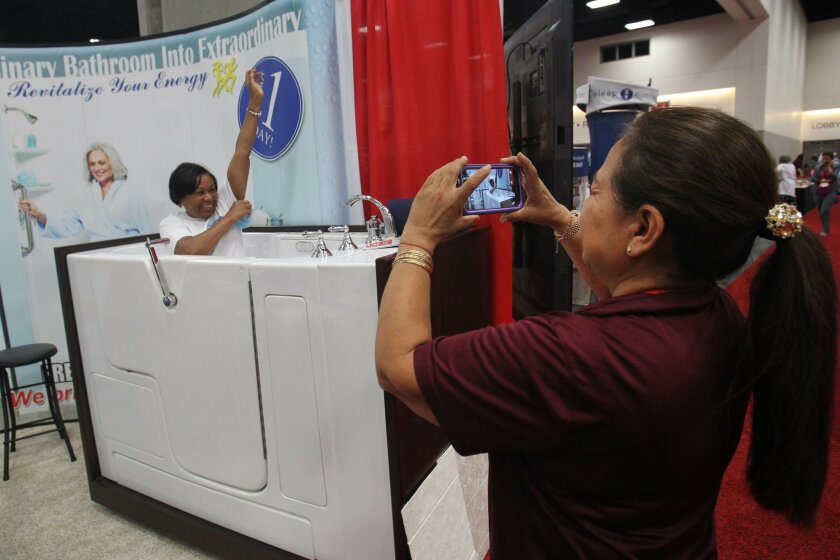 There were plenty of things for the senior set, as well as younger baby boomers on the exhibit floor of the Ideas@50+ AARP convention at the San Diego Convention Center Friday. Olga Escalante, with Reborn Cabinets, takes a picture of conventioneer Tammy Ansah-Yiadom of Houston, as she sat inside of