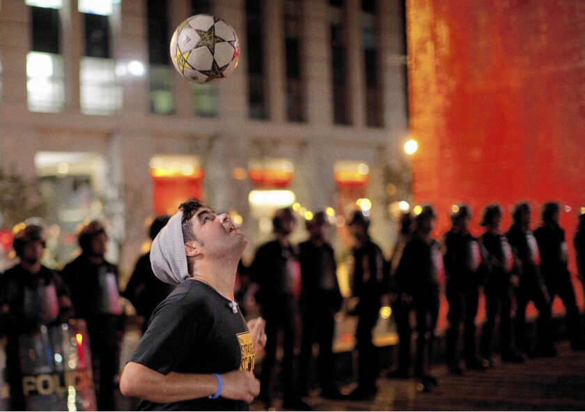 A protester plays with a soccer ball as riot police stand guard in Sao Paulo, Brazil. Hundreds gathered to demand the release of two people arrested during an earlier protest.