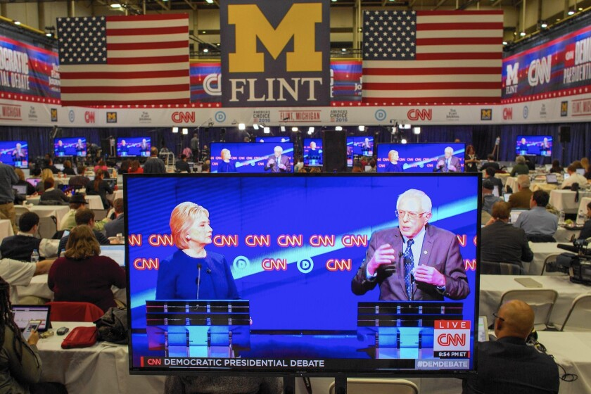 A debate between Hillary Clinton and Bernie Sanders is seen on a TV in the press room in Flint, Mich.