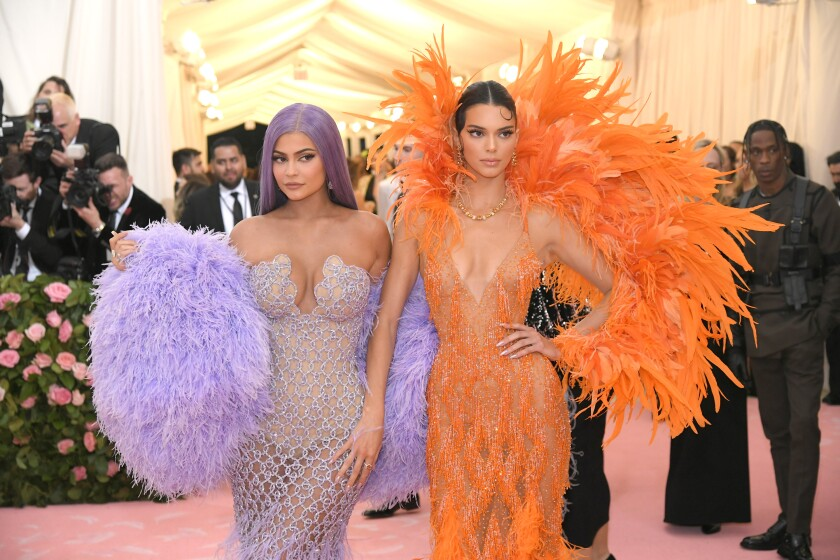 A woman in a feathery purple dress poses with a woman in a feathery orange dress