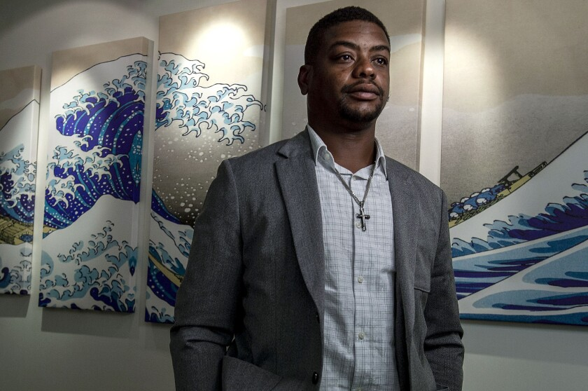 """""""You can't treat people differently just because of their religion or skin color,"""" said Jeffrey Ryans in his attorney's office, Aug. 5, 2020, in Salt Lake City. A Salt Lake City police officer who ordered a dog to attack Ryans, who had already put his hands in the air has been charged with aggravated assault, the district attorney's office said Wednesday, Sept. 16. Prosecutors say Ryans was in his backyard on April 24 when police were called to his home for an alleged domestic dispute. (Leah Hogsten/The Salt Lake Tribune via AP)"""