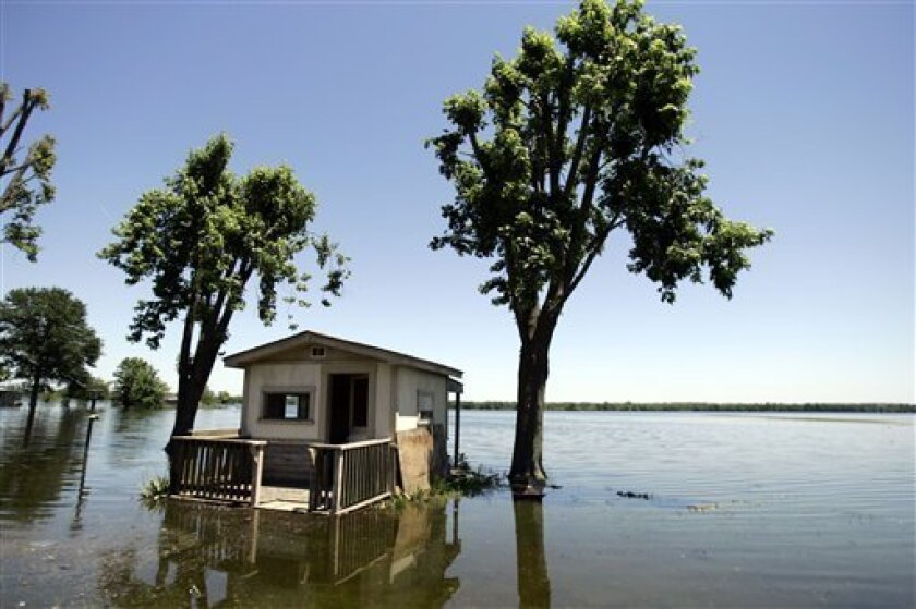 FILE- In this file photo taken Monday, June 23, 2008, floodwater from the Mississippi River surrounds a small shed behind a house in Foley, Mo. With the world losing the battle against global warming so far, experts say humans need to do what nature does: Adapt or die. (AP Photo/Jeff Roberson, File)