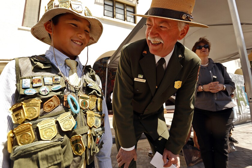 Special programs are planned during National Park Week for Junior Park Rangers like young Tigran Nahabedian, left, who had collected 32 ranger badges when he met National Service Director Jonathan Jarvis last year at the El Pueblo de Los Angeles Historic Monument in L.A.