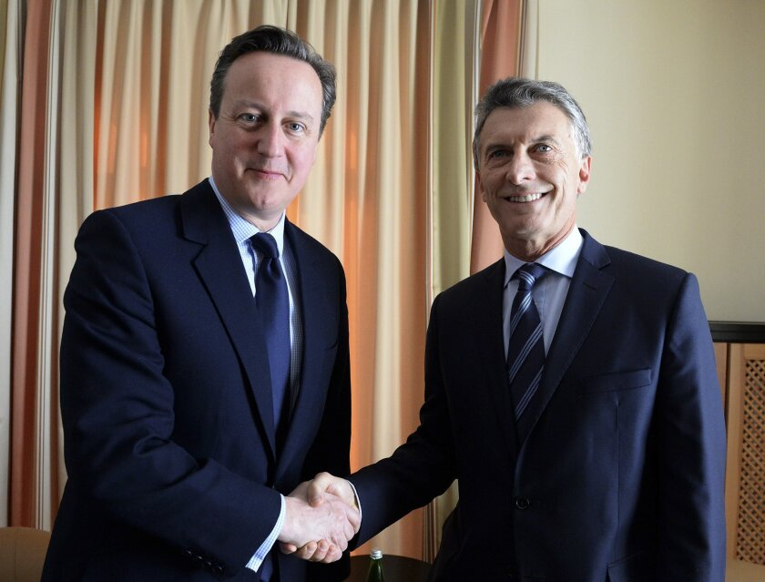 In this handout picture released by the Office of the President of Argentina, President Mauricio Macri, right, shakes hands with British Prime Minister David Cameron, during a meeting of the World Economic Forum in Davos, Switzerland, Thursday, Jan. 21, 2016. (The Office of the President of Argentina Photo via AP)