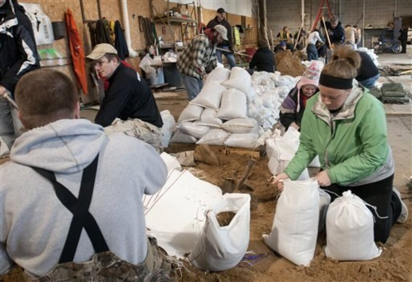 Holli McPherson, right, and other volunteers help fill sandbags inside a Grand Rapids City maintenance garage on Market Street in Grand Rapids, Mich., Friday, April 19, 2013. She and other WMEAC volunteers were planning to take part in the annual Grand River clean-up but instead helped with flood control. Volunteers plan to work through the weekend in Grand Rapids to fill sandbags as part of an effort to hold off West Michigan floodwaters. (AP Photo/The Grand Rapids Press, Chris Clark) ALL LOCAL