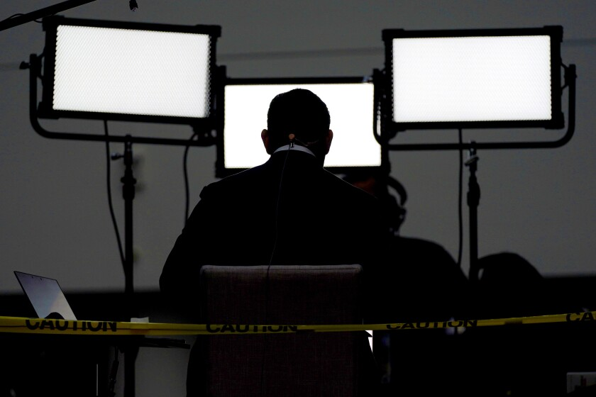FILE - In this Sept. 29, 2020, file photo a broadcast journalist sits in front of lights ahead of the first presidential debate between Republican candidate President Donald Trump and Democratic candidate former Vice President Joe Biden at the Health Education Campus of Case Western Reserve University in Cleveland. A new study of people's attitudes toward the press finds that distrust goes deeper than just partisanship and down to how journalists define their mission. Americans want their journalists to be more than watchdogs. (AP Photo/Julio Cortez, File)