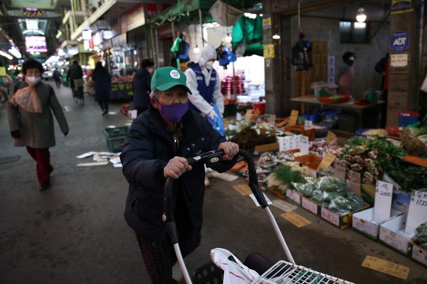 An elderly South Korean man wearing a ball cap and face masks walks in a Seoul market, pushing a cart.