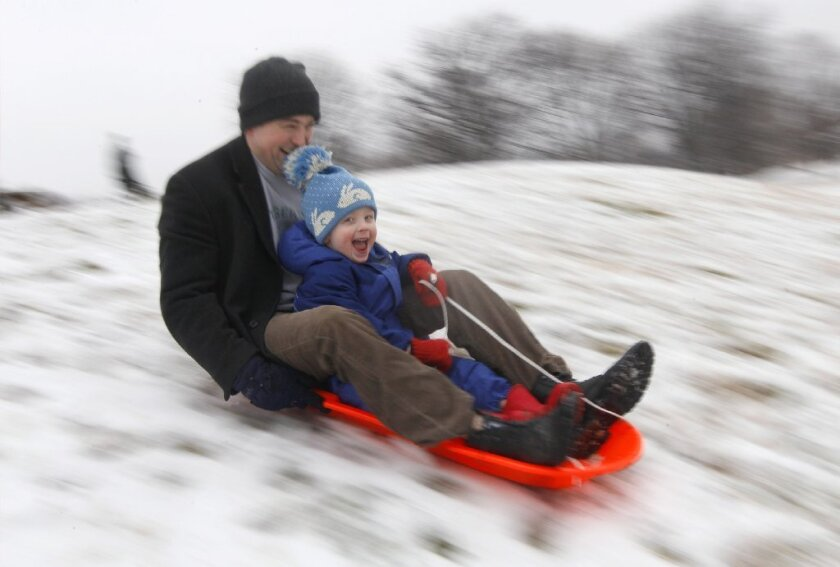 Mike Redmond and his 3-year-old son, Matt, ride a sled down a hill after an overnight snowfall in Baltimore in 2012.