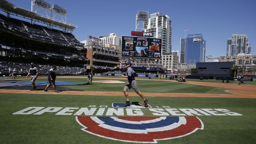A groundskeeper runs over the logo before an opening day baseball game between the San Diego Padres and the Milwaukee Brewers in San Diego,