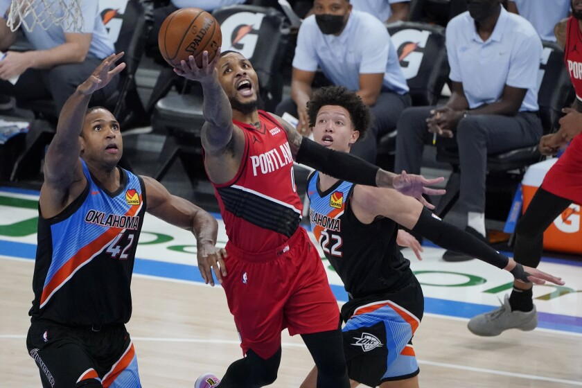 Portland Trail Blazers guard Damian Lillard (0) shoots between Oklahoma City Thunder center Al Horford (42) and center Isaiah Roby (22) in the second half of an NBA basketball game Tuesday, Feb. 16, 2021, in Oklahoma City. (AP Photo/Sue Ogrocki)