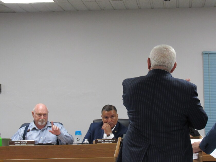 Lemon Grove City Councilman Jerry Jones (left) shares some of his frustrations about how many homes the city is being asked to build with San Diego Association of Governments Executive Director Hasan Ikhrata (front) as City Councilman David Arambula looks on during a City Council meeting on Aug. 20 in Lemon Grove.