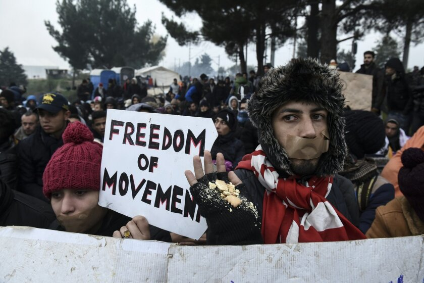 Migrants and refugees stage a protest demanding to be allowed to cross the border with Macedonia, near the Greek village of Idomeni, Saturday, Nov. 21, 2015. Tempers have flared at Greece's main border crossing with Macedonia, where riot police pushed back thousands of migrants jostling to cross over, after Macedonia blocked access to people deemed to be economic migrants and not refugees. (AP Photo/Giannis Papanikos)