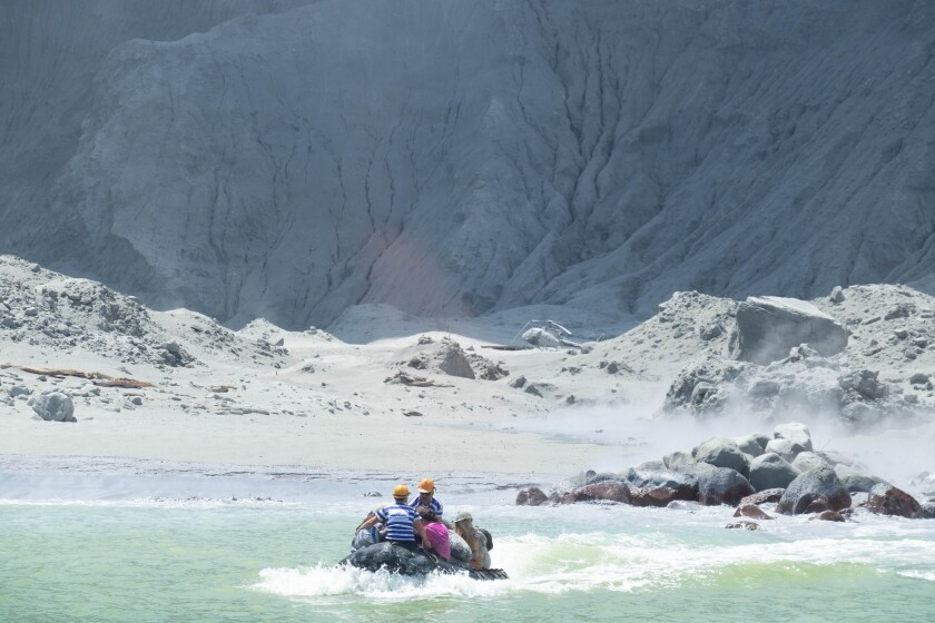 Tourists aboard a boat leave New Zealand's White Island volcano, which erupted.