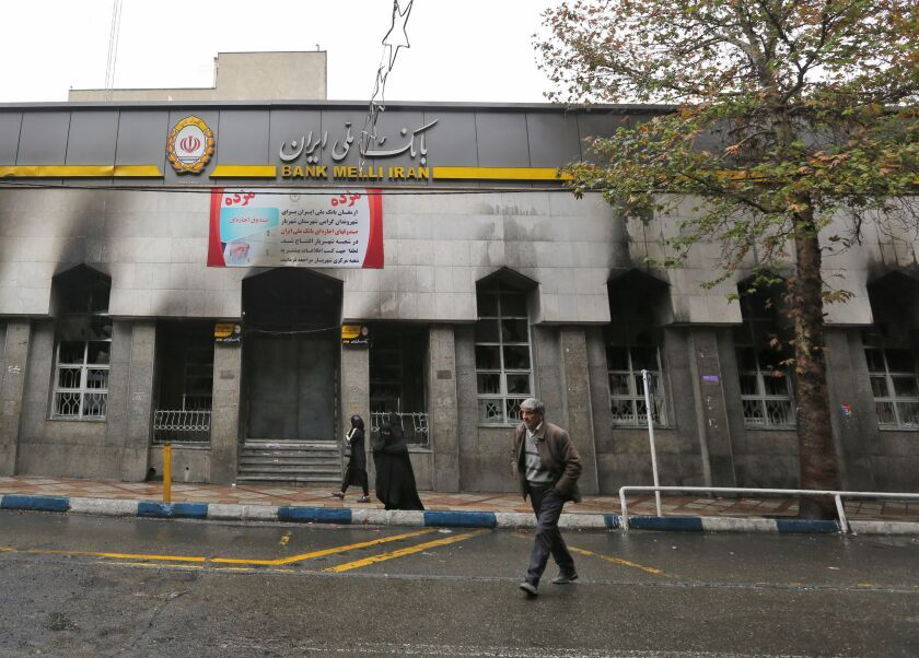 Iranians on Thursday walk past a bank in Shahriar that was damaged during demonstrations against gasoline price hikes.