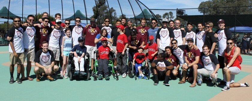 Members of Pi Kappa Alpha and TVIA SD2 teens are assisting the Miracle League athletes at their ballgames.
