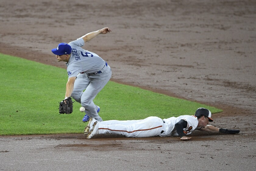 Baltimore's Austin Hays slides into second base as Dodgers shortstop Corey Seager can't catch the pickoff throw during Wednesday's 7-3 loss.