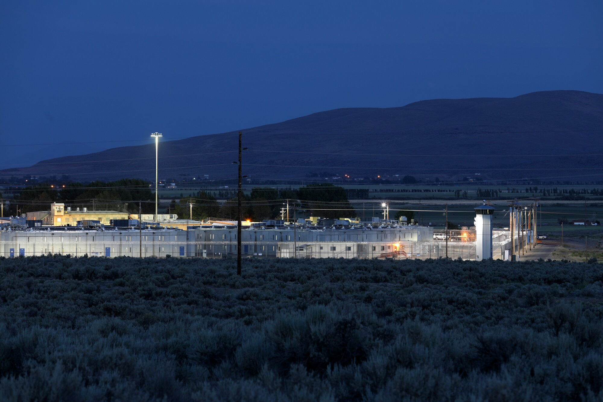 A view from a distance of a fence-enclosed prison at dusk.