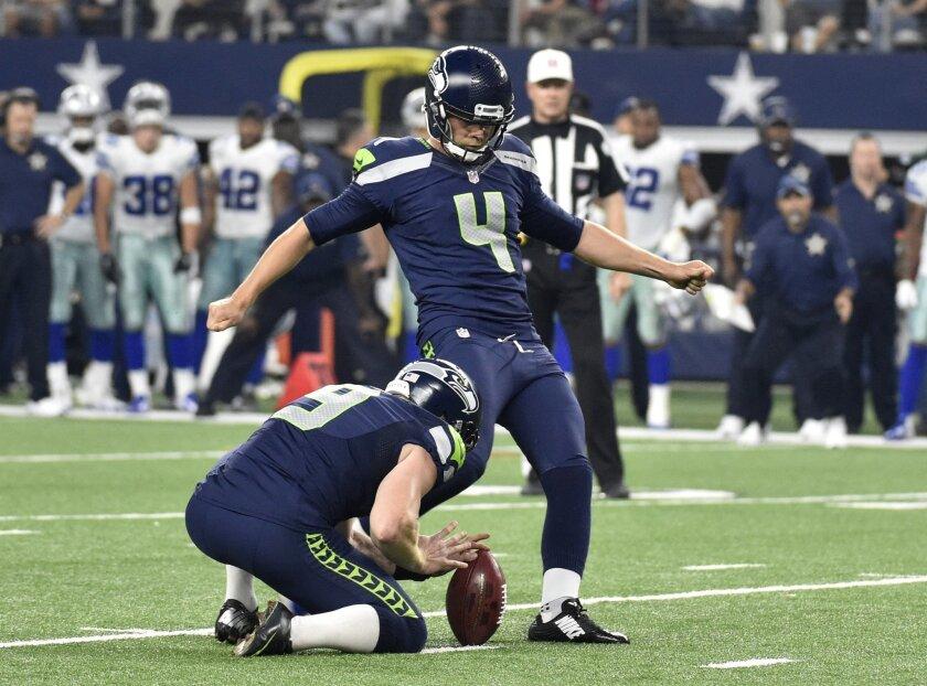 Seattle Seahawks' Jon Ryan (9) holds as kicker Steven Hauschka (4) boots a field goal in the second half of an NFL football game against the Dallas Cowboys, Sunday, Nov. 1, 2015, in Arlington, Texas. (AP Photo/Michael Ainsworth)