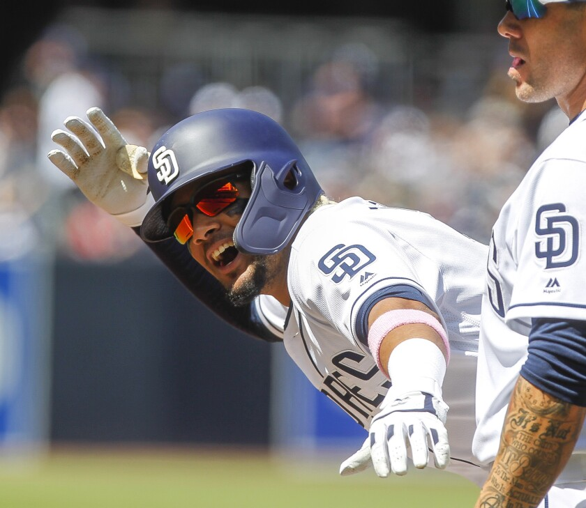 While standing next to first base coach Skip Schumaker, the Padres' Fernando Tatis Jr. looks toward the dugout as he celebrates at first base after he hit a single during second inning of the Padres' home opener against the Giants at Petco Park on March 28, 2019.