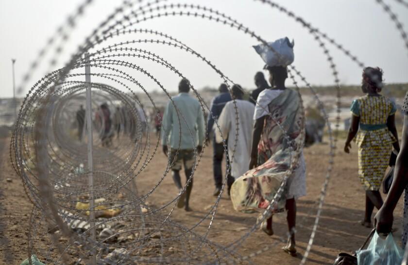 ARCHIVO - En esta imagen de archivo, gente desplazada camina junto a un alambre de cuchillas en la base de Naciones Unidas en la capital de Sudán del Sur, Yuba. (AP Foto/Jason Patinkin, Archivo)