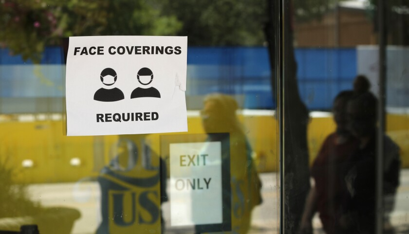 The images of passersby are reflected next to a sign requiring face coverings at a business in San Antonio, Texas.