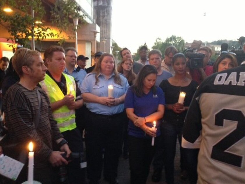 BART workers gather at a Sunday evening vigil for two employees struck and killed by a train on Saturday.