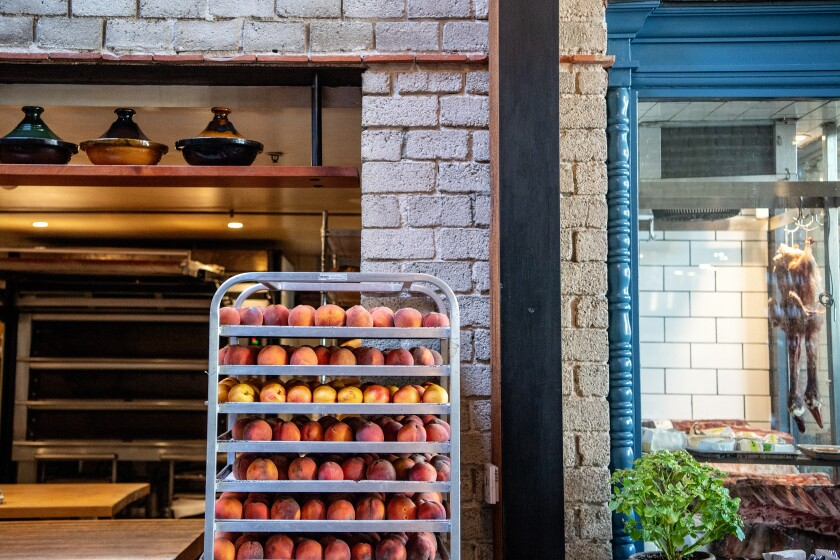 Stone fruits ripening on a tiered metal rack at République