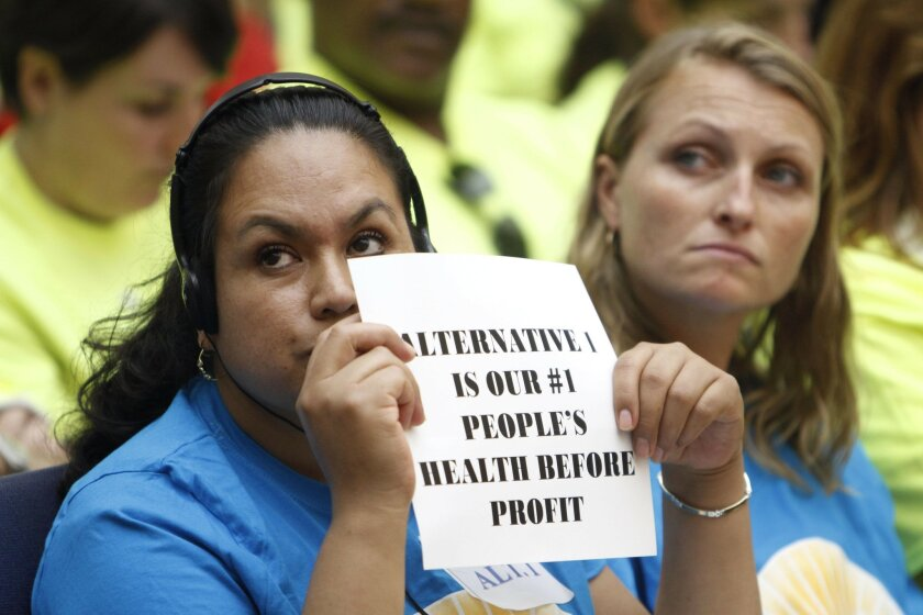 Barrio Logan resident Maria Martinez holds a sign as she and Livia Borak, an attorney, support the Barrio Logan community plan update being discussed during a San Diego City Council meeting in September.