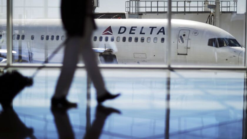 FILE - In this Oct. 13, 2016, file photo, a Delta Air Lines jet sits at a gate at Hartsfield-Jackson