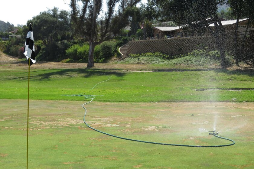A lone sprinkler connected to a home hundreds of feet away tries to keep a green at the Fallbrook Golf Club alive