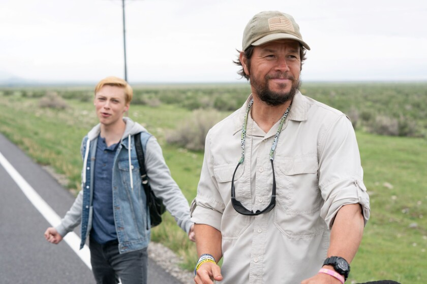 A teenage boy and his father on the side of a rural highway