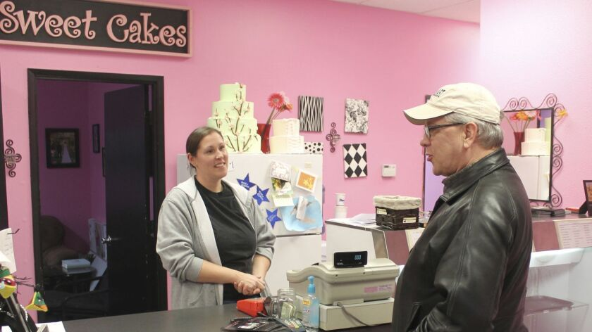Melissa Klein, co-owner of Sweet Cakes by Melissa, in Gresham, Ore., speaks with a customer in February 2013.