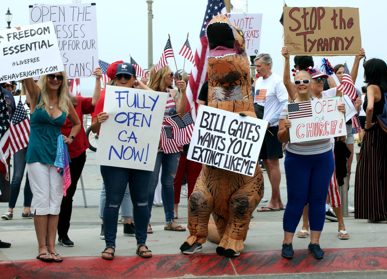 Protesters hold signs with various messages during Saturday's protest to open the state of California at Pier Plaza in Huntington Beach.