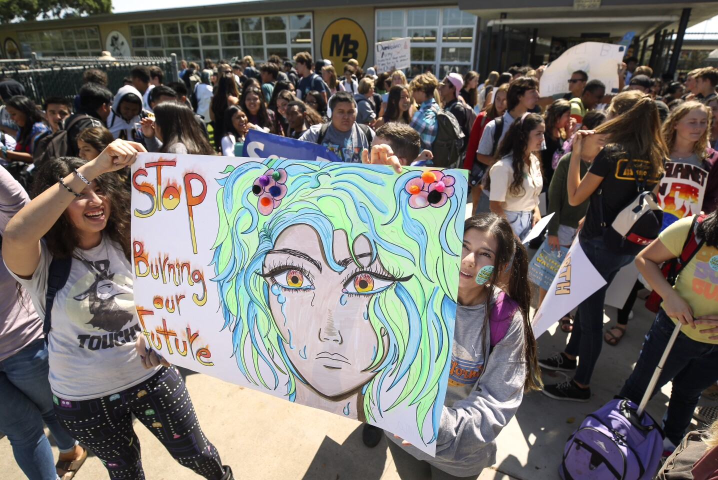 Izabella Speinbock, left, and Fatima Jaser, both 17 and seniors, hold a sign as they and fellow students gather in front of Mission Bay High School after they walked out of classes to participate in the Global Climate Strike on Friday, September 20, 2019 in San Diego, California.