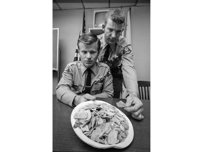 April 5, 1970: Potato and corn chips spiked with LSD at a Marina del Rey party are viewed by Los Angeles County sheriff's deputies James T. Lyle, left, and Lonnie J. Pierce.